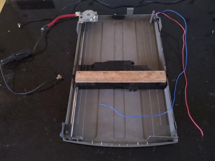 The base with the scan head of an old flatbed scanner, with the stepper motor and limit switch attached.